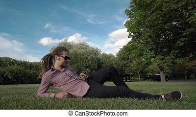 makes selfie in a public park: smart phone, photo - man with...
