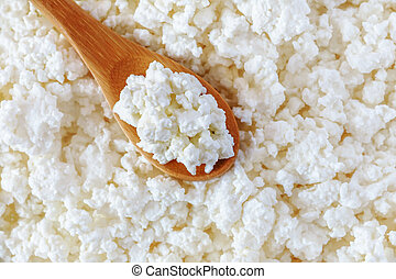 crumbly cottage cheese in the wooden spoon lying diagonally...