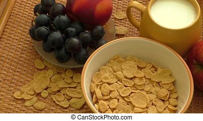 Corn flakes and milk falling in a bowl