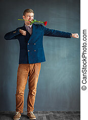 Handsome young man dancing with a red rose in his mouth