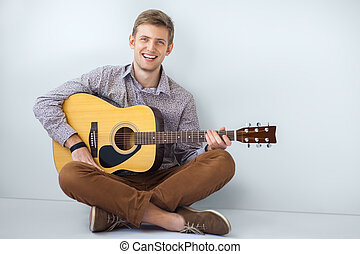 Portrait of happy handsome man playing guitar siting on...