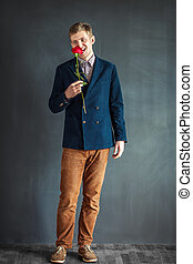 Full length portrait of funny man eating red rose standing...