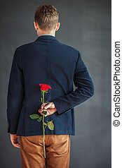 Rear view of young man holding red rose behind his back...
