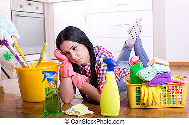 Tired cleaning lady - Tired young woman lying on stomach on...