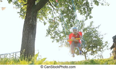 Cute baby boy playing on swing in summer garden. Swings are attached to the tree