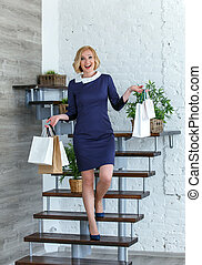 Young happy smiling woman with shopping bags on the stairs