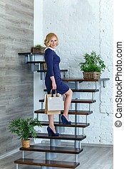 Young blond elegant woman with shopping bags on the stairs