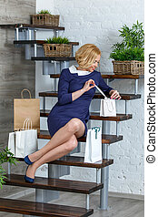 Young blond elegant woman unpacking her shopping bags on the...