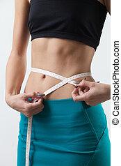 Measuring waist circumference - Girl measuring waist...