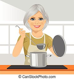 Smiling mature woman with ladle cooking soup in pan at domestic kitchen