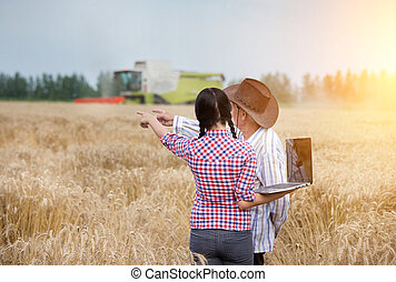 People at harvest - Young farmer girl with laptop standing...