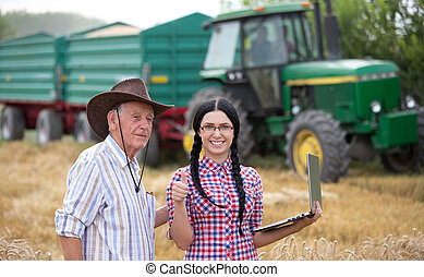 People at harvest - Young smiling farmer girl with laptop...