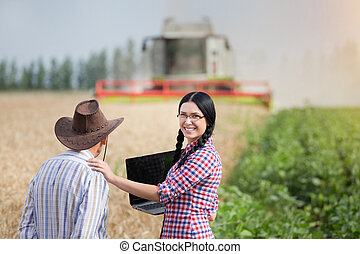 People at harvest - Young pretty farmer girl with laptop...