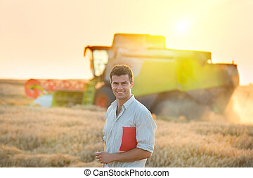 People at harvest - Young attractive farmer with notebook in...