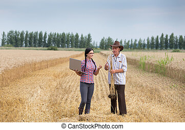 People at harvest - Senior man and young woman with laptop...