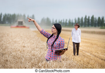 Farmer girl with laptop at harvest - Young farmer girl with...