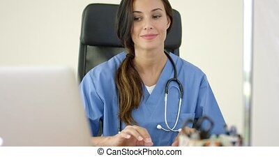 Beautiful female doctor at laptop computer - Beautiful...