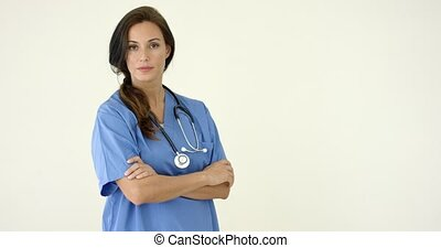 Woman in scrubs crosses arms and smiles at camera with...