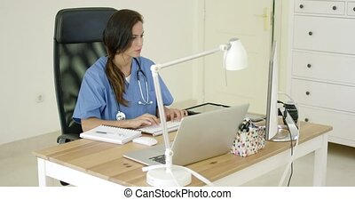 Young female doctor sitting typing in her office as she...