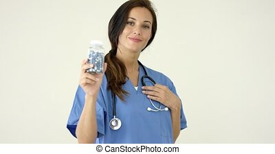 Young brown haired doctor in scrubs holds bottle