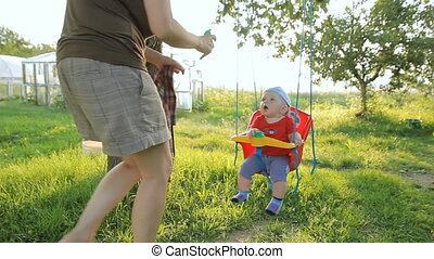 Cute curly baby boy having fun on a swing with mother