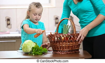 girl helps her mother pulling vegetables from the basket