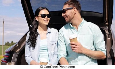happy couple with coffee at hatchback car trunk - travel,...