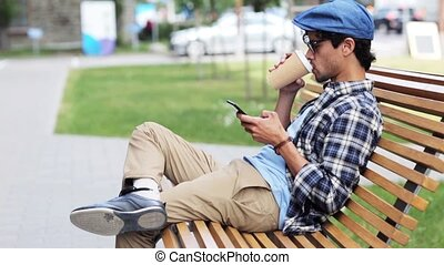 man with smartphone drinking coffee on city street -...