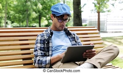 man with tablet pc sitting on city street bench 45 -...