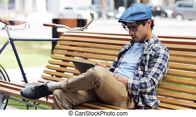 man with tablet pc sitting on city street bench 29 -...