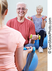 Seniors At Fitness Class With Instructor