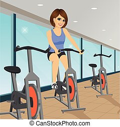 young woman doing indoor biking exercise at gym