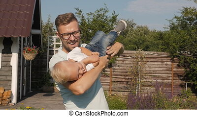 Happy Dad Having Fun With His Little Smiling Son In The Garden