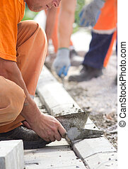 Worker installing curb stones - Construction worker filling...