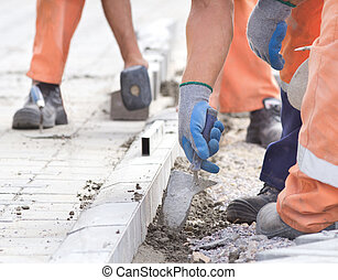 Worker installing curb stones - Construction worker...
