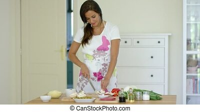 Attractive young woman cooking in the kitchen at home...