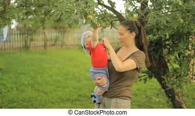 Little baby boy with her young mother play with apple tree