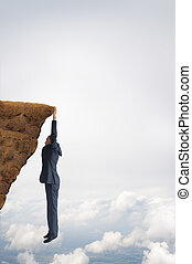 business challenge concept businessman clinging on to a...