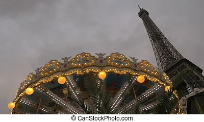 Vintage carousel and Eiffel Tower in the evening - Low angle...