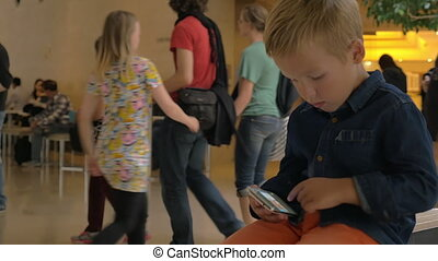 Kid looking at photos on mobile phone in trade centre