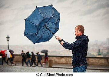 Man in rainy day - Rain in the city. Young man is holding...