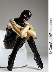 woman in latex sitting on the chair