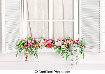 Blooming flower bed under the window. Windowsill with...