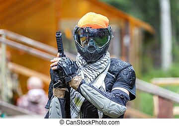 Cool paintball fighter in special armor holding paint handgun.