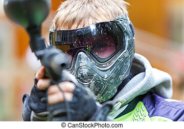 Handsome paintball player aiming in camera. Closeup.