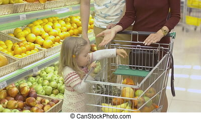 Family makes purchases in the supermarket. Little girl...