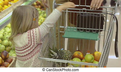 Little girl puts fruits in the trolley in the supermarket