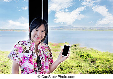 Asian women smiling presenting smartphone or cellphone in...