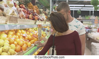 Couple makes purchases in the supermarket - Couple chooses...