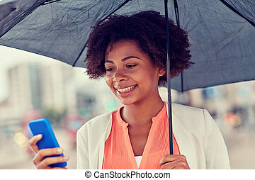 businesswoman with umbrella texting on smartphone -...